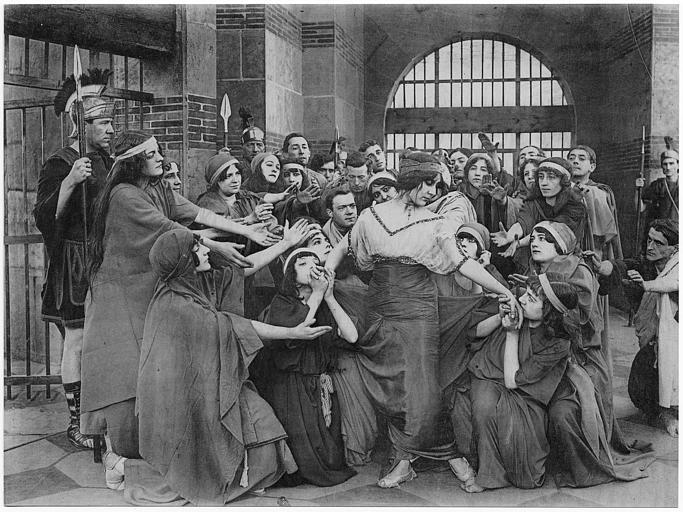 Dans une prison à l'époque antique, une femme entourée de plusieurs personnages dont la majorité sont des femmes