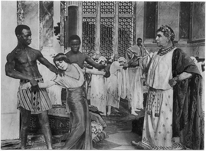 Une femme saisie par deux hommes noirs devant un magistrat romain