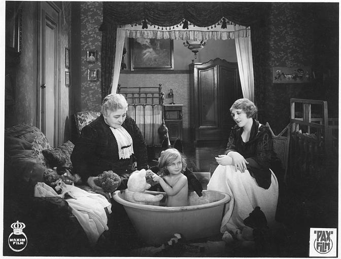 Deux femmes autour d'une fillette se baignant dans un salon dans 'Tragödie einer Ehe' de Maurice Elvey