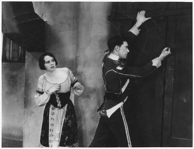 Un homme forçant une porte avec une femme derrière lui : Benita Hume interprète Jean McDonald et Cyril McLaglen joue John Kennedy dans 'Balaclava' de Maurice Elvey et Milton Rosmer