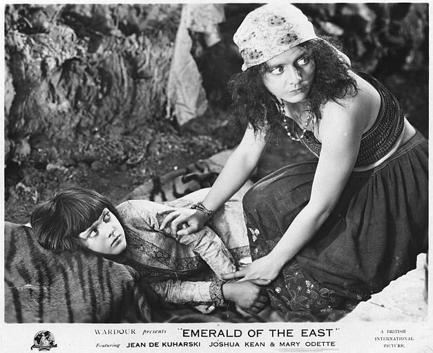 Une femme s'accroupissant près d'une enfant couchée sur le sol : Mary Odette dans le rôle de Nellum et Joshua Kean dans celui de Desmond Armstrong dans 'Emerald of the east' de Jean de Kuharski (British International Pictures)