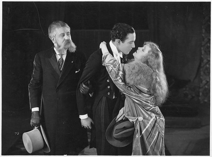 Flora Le Breton dans le rôle de Raymonde au cou de Pierre Batcheff qui joue Sacha qu'un deuxième homme attire vers lui en le tirant par le bras dans 'Education de prince' d'Henri Diamant-Berger