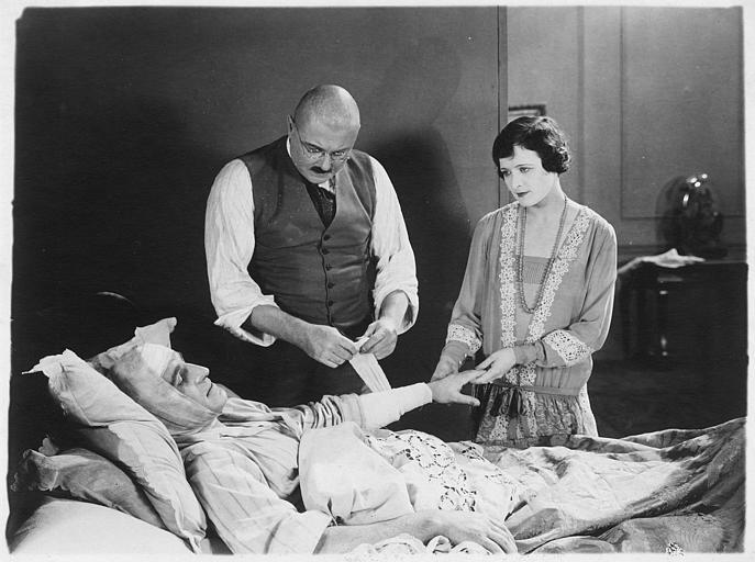 Lilian Hall-Davies dans le rôle de Sonia au chevet d'un homme blessé pansé par un homme chauve dans 'Nitchevo' de Jacques de Baroncelli