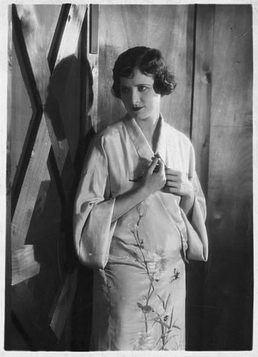 Lillian Hall-Davies, jouant la châtelaine, debout portant une robe de type asiatique dans 'La proie du vent' de René Clair