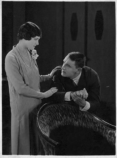 Lillian Hall-Davies discutant avec un homme appuyé sur un fauteuil