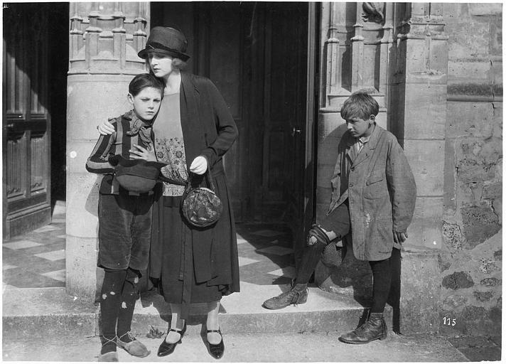 Marjorie Hume dans le rôle de Marion Thornton sur le pas d'une porte avec deux enfants vagabonds, Dick interprété par Leslie Shaw et Wally par Jean Forrest dans 'Les deux gosses' de Louis Mercanton