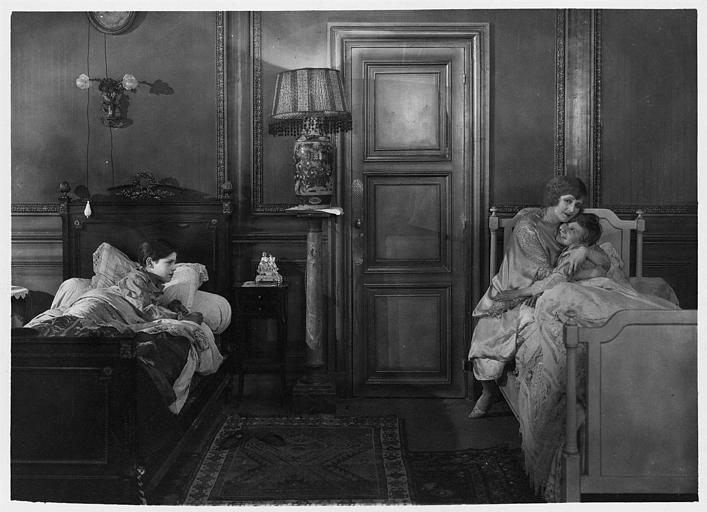 Marjorie Hume dans le rôle de Marion Thornton dans une chambre avec deux garçons dans leur lit, Dick interprété par Leslie Shaw qu'elle serre dans ses bras et Wally interprété par Jean Forrest dans 'Les deux gosses' de Louis Mercanton