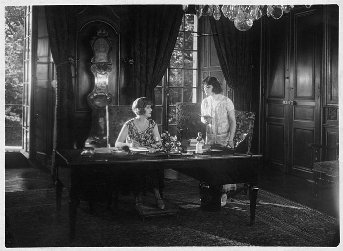 Marjorie Hume dans le rôle de Marion Thornton assise à un bureau et Gina Relly interprétant Barbara Scarth lui lisant un mot debout à ses côtés dans 'Les deux gosses' de Louis Mercanton
