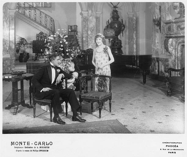 Dans un hall, un homme assis et Betty Balfour interprétant Violette Olivier, debout, souriant dans 'Monte-Carlo' de Louis Mercanton (Cinématographes Phocéa)