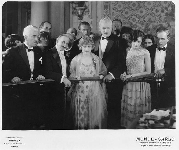 Betty Balfour dans le rôle de Violette Olivier et Charles Lamy dans celui du Marquis de Villiers entourés de nombreux personnages derrière une rambarde métallique dans 'Monte-Carlo' de Louis Mercanton (Cinématographes Phocéa)