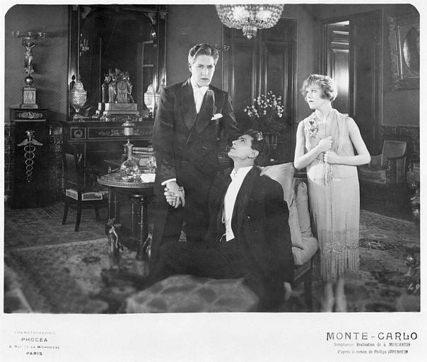 Dans un riche salon, Betty Balfour dans le rôle de Violette Olivier en présence de Carlyle Blackwell interprétant Sir Hargrave Wendever et d'un deuxième homme dans 'Monte-Carlo' de Louis Mercanton (Cinématographes Phocéa)
