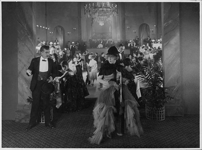 Dans un music-hall, Betty Balfour discute avec André Nox