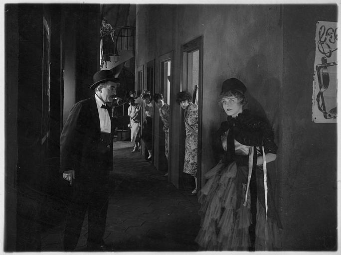 Dans les coulisses d'un music-hall, Betty Balfour discute avec André Nox