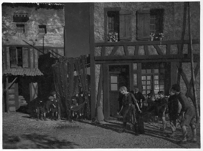 Dans une rue de village de bord de mer, Betty Balfour entourée d'enfants