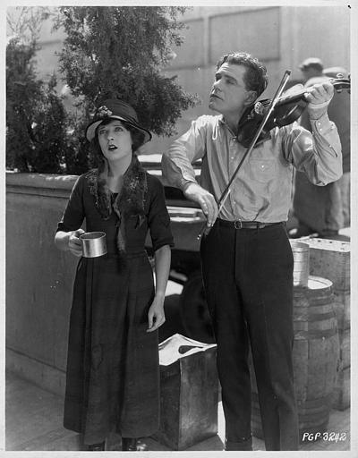 Dans la rue, May McAvoy dans le rôle de Myrtle chante pour gagner de l'argent, tandis que Bert Lytell dans le rôle de Chick Hewes l'accompagne au violon dans 'Kick In' de Georges Fitzmaurice (Paramount Picture)