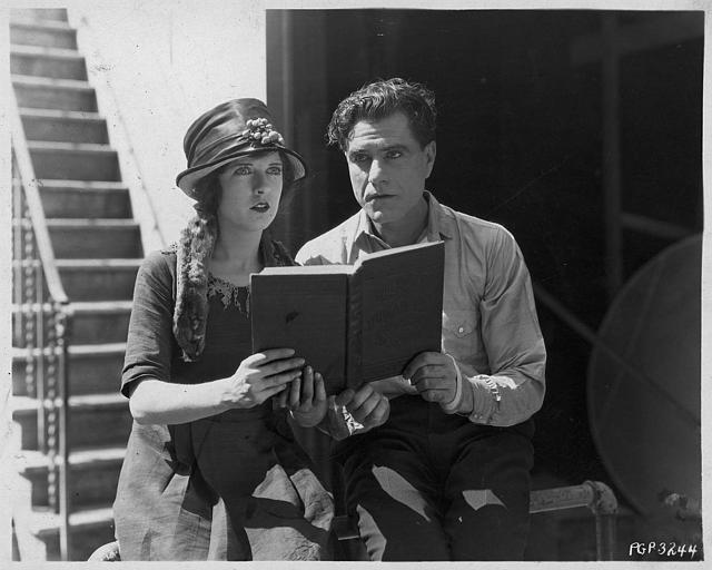 May McAvoy dans le rôle de Myrtle et Bert Lytell dans le rôle de Chick Hewes lisant un livre dans 'Kick in' de Georges Fitzmaurice (Paramount Picture)