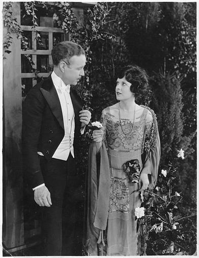 Un couple dans un jardin :  May McAvoy est Virginia Bullivant dans 'Grumpy' de  William C. DeMille