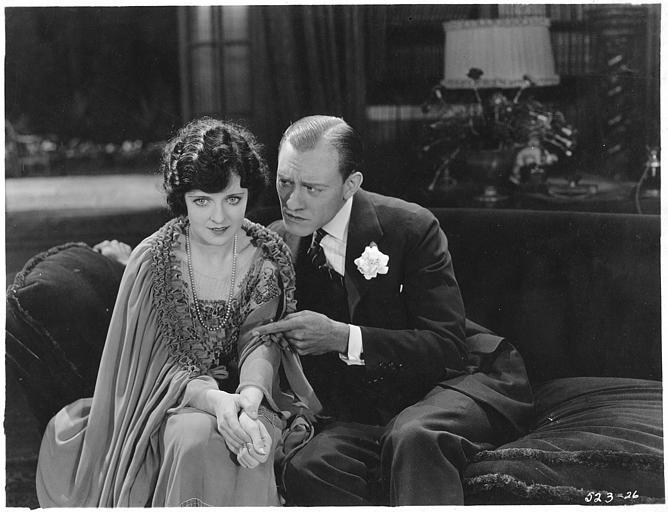 Un couple dans un salon assis sur un canapé :  May McAvoy est Virginia Bullivant dans 'Grumpy' de  William C. DeMille