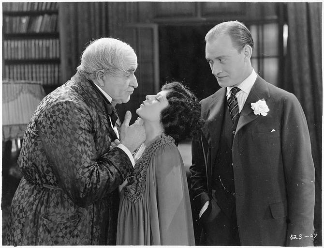 May McAvoy dans le rôle de Virginia Bullivant mimant un baiser à un homme plus âgé, en présence d'un autre homme dans 'Grumpy' de  William C. DeMille