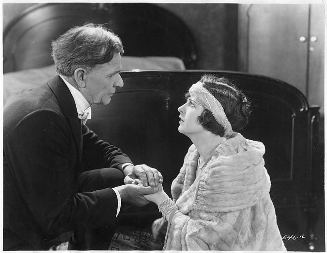 May McAvoy dans le rôle de Ruth Martin suppliant un homme plus âgé qu'elle au pied d'un lit dans ' The bedroom window' de William C. DeMille