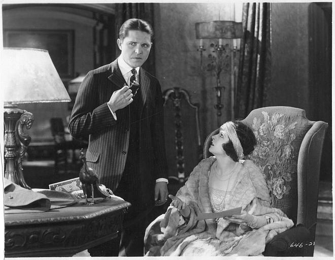 May McAvoy dans le rôle de Ruth Martin, assise dans un fauteuil et un homme debout à côté dans un salon dans ' The bedroom window' de William C. DeMille