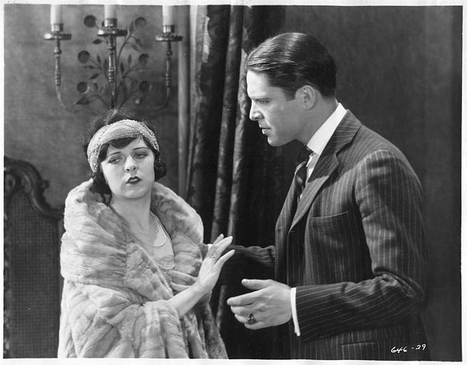 May McAvoy dans le rôle de Ruth Martin, faisant un geste de refus à un homme en costume rayé dans ' The bedroom window' de William C. DeMille