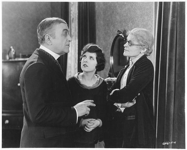 May McAvoy dans le rôle de Ruth Martin entre un couple plus âgé discutant dans ' The bedroom window' de William C. DeMille