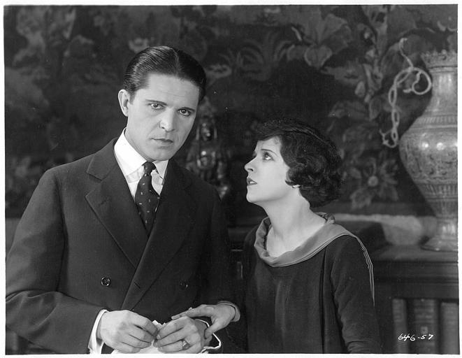 May McAvoy dans le rôle de Ruth Martin posant sa main sur celle d'un homme pensif dans ' The bedroom window' de William C. DeMille