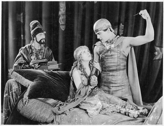 Une homme levant son poing devant May McAvoy jouant Esther assise sur un lit dans 'Ben-Hur' de Fred Niblo (Metro-Goldwyn-Mayer)