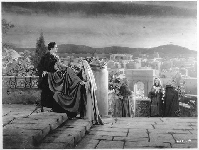 Plusieurs femmes montant un escalier où un jeune homme les attend avec en fond un décor de ville dans 'Ben-Hur' de Fred Niblo (Metro-Goldwyn-Mayer)