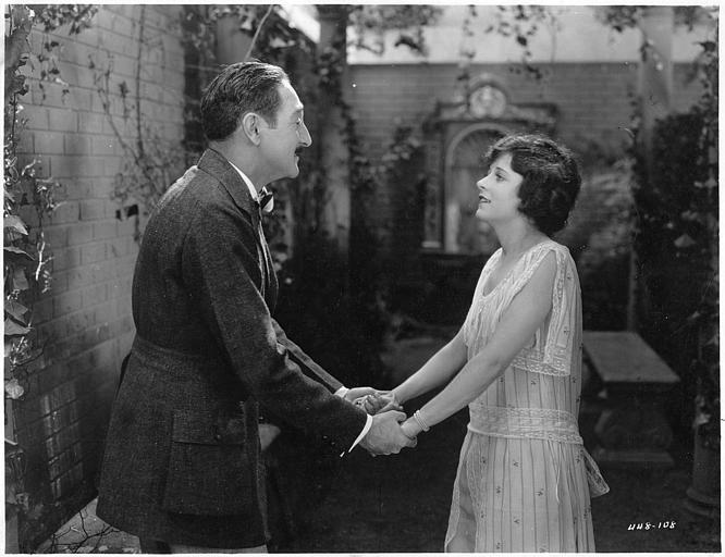 Dans un jardin, Adolphe Menjou (Hubert Stein) et May McAvoy (Cora Wheeler) se tiennent par les mains  dans 'Clarence' de William C. DeMille