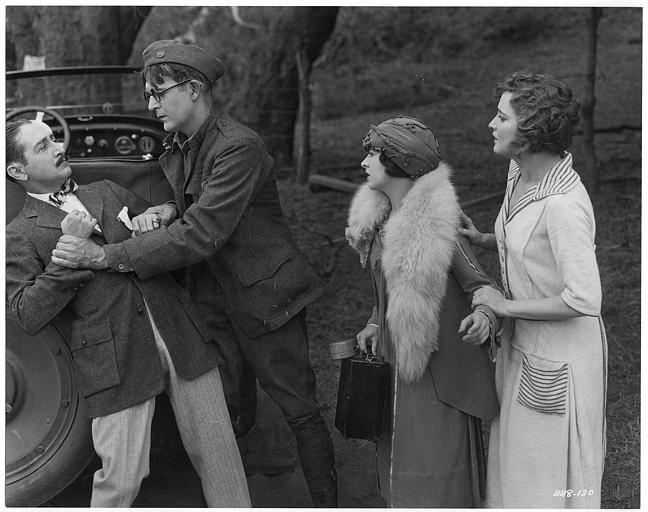 Adolphe Menjou (qui interprète Hubert Stein) et Wallace Reid (Clarence Smith) se battent sur le capot d'une voiture en présence de May McAvoy (Cora Wheeler) et Agnès Ayres (Violet Pinney) dans 'Clarence' de William C. DeMille