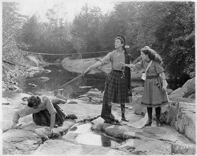 Dans le lit d'une rivière, Gareth Hughes dans le rôle de Tommy Sandys et George Fawcett dans celui du Dr. McQueen, en kilt, se battent en présence de Mabel Taliaferro dans 'Sentimental Tommy' de John S. Robertson