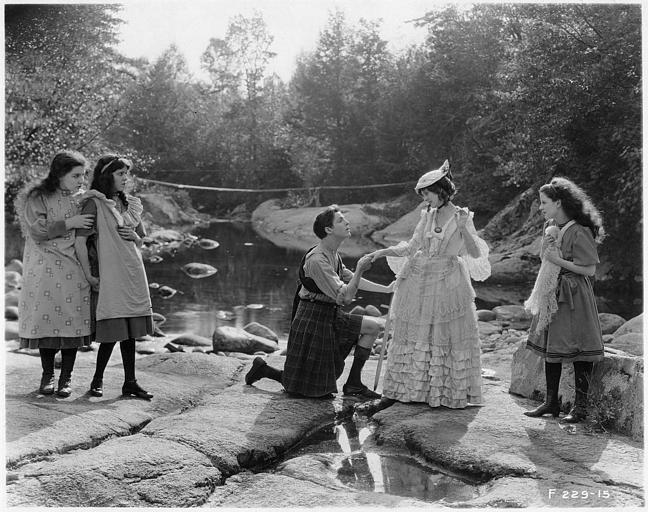 Un homme en kilt à genoux devant May McAvoy dans le rôle de Grizel en présence de trois jeunes filles dans 'Sentimental Tommy'  de John S. Robertson