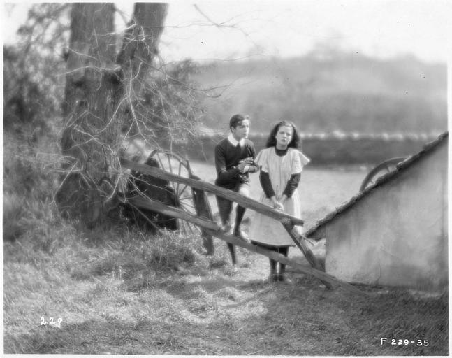 May McAvoy dans le rôle de Grizel suivie par un homme devant une barrière dans un champs dans 'Sentimental Tommy'  de John S. Robertson