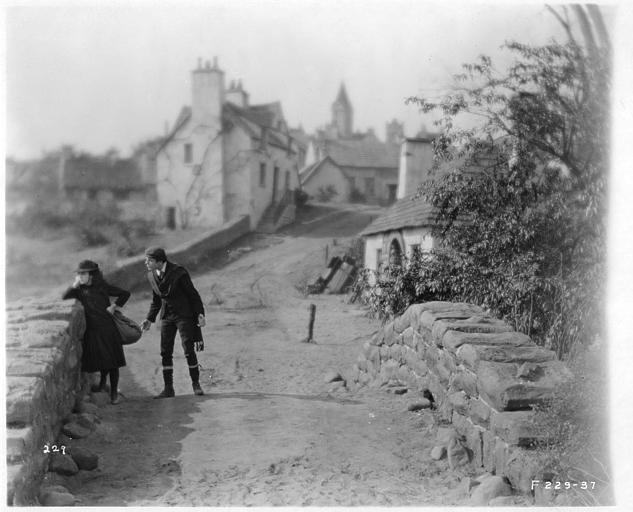 May McAvoy dans le rôle de Grizel accoudée sur un pont de pierre tandis qu'un homme lui parle dans 'Sentimental Tommy' de John S. Robertson