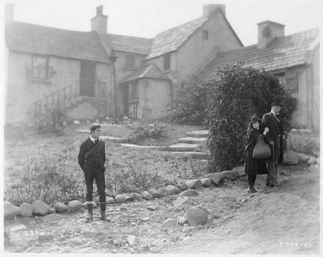 May McAvoy dans le rôle de Grizel au bras d'un homme plus âgé marchant avec une canne et un jeune homme dans la cour d'une ferme dans 'Sentimental Tommy' de John S. Robertson