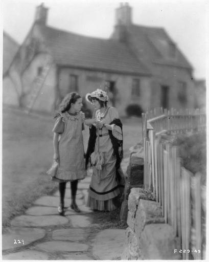 May McAvoy dans le rôle de Grizel et une jeune fille lisant une carte sur un trottoir en pierre le long d'une barrière dans 'Sentimental Tommy' de John S. Robertson