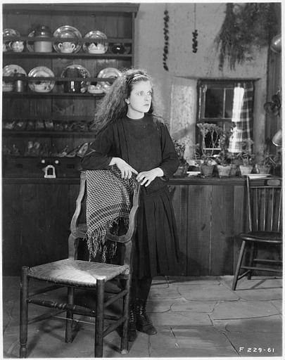 May McAvoy dans le rôle de Grizel en noir appuyée sur une chaise dans 'Sentimental Tommy'  de John S. Robertson