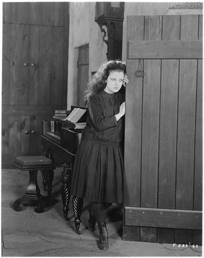 May McAvoy dans le rôle de Grizel en noir appuyée contre une porte dans 'Sentimental Tommy'  de John S. Robertson
