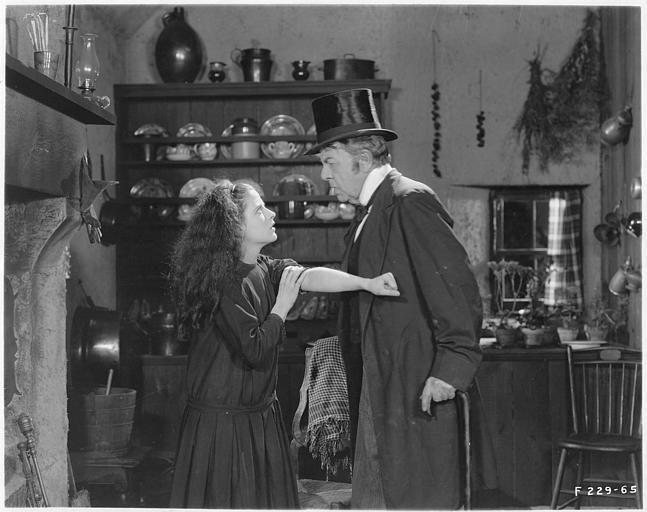 May McAvoy dans le rôle de Grizel montrant son avant bras à un homme plus âgé qu'elle dans une cuisine dans 'Sentimental Tommy' de John S. Robertson