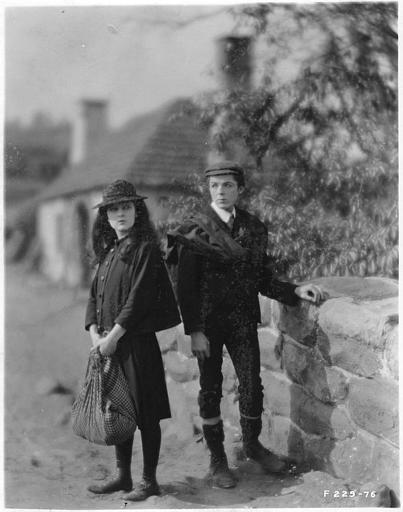 May McAvoy dans le rôle de Grizel, tenant son baluchon, et un jeune homme sur un pont de pierre dans 'Sentimental Tommy' de John S. Robertson