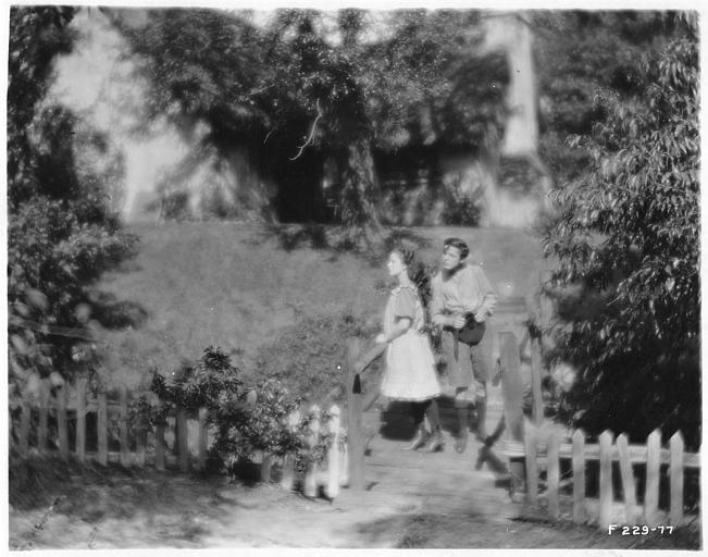Deux jeunes personnages sur un petit pont de bois dans un jardin dans 'Sentimental Tommy' de John S. Robertson