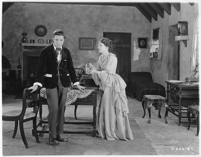 Une femme montrant une paire de ganst à un jeune homme dans un salon dans 'Sentimental Tommy' de John S. Robertson