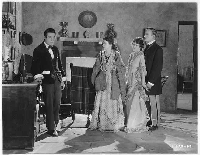 Un jeune homme appuyé sur un commode tandis que May McAvoy dans le rôle de Grizel et un couple le regardent dans 'Sentimental Tommy' de John S. Robertson