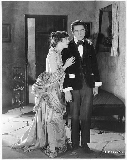 Une femme réconfortant un jeune garçon dans une entrée dans 'Sentimental Tommy' de John S. Robertson