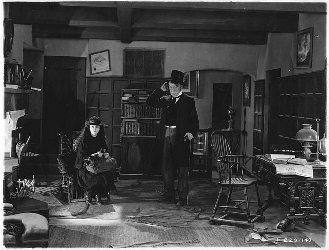 May McAvoy dans le rôle de Grizel assise et un homme portant un chapeau haut-de-forme et se grattant la tête debout à ses côtés dans 'Sentimental Tommy' de John S. Robertson