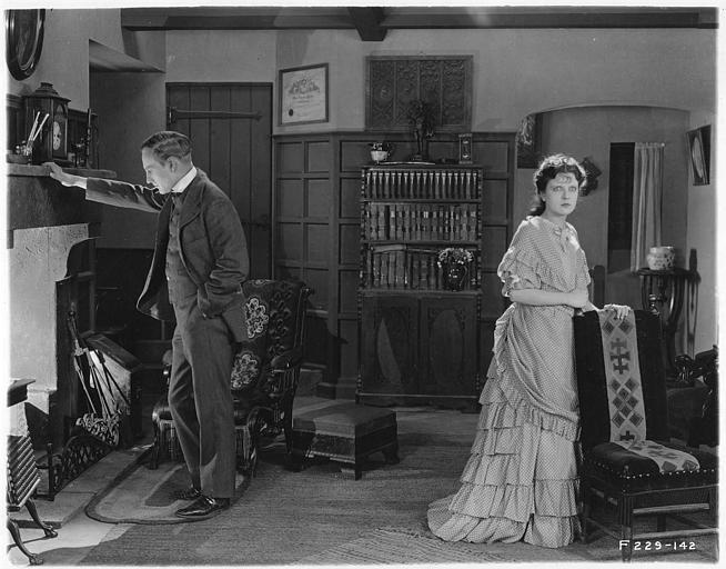 Un homme appuyé contre une cheminée avec May McAvoy dans le rôle de Grizel dans 'Sentimental Tommy' de John S. Robertson