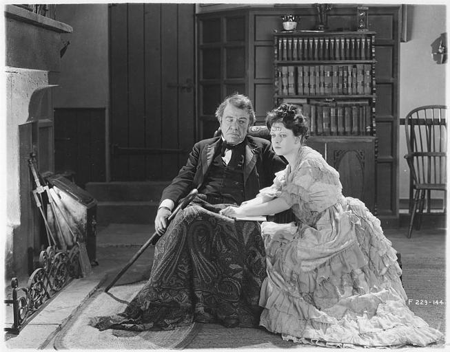 Un vieil homme dans un fauteuil près du feu avec May McAvoy dans le rôle de Grizel à ses genoux dans 'Sentimental Tommy' de John S. Robertson