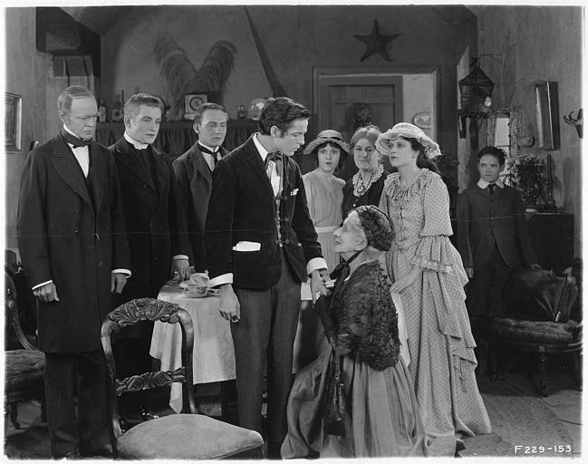 Groupe de personnages dont May McAvoy dans le rôle de Grizel autour d'un jeune homme devant lequel une femme âgée est à genoux dans un salon dans 'Sentimental Tommy' de John S. Robertson